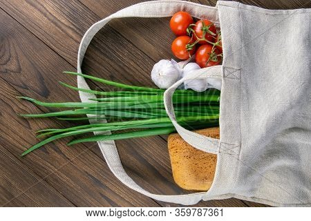 Woven Bag Of Different Health Food On Dark Wooden Table Background. Bread, Green Onion, Garlic, Toma