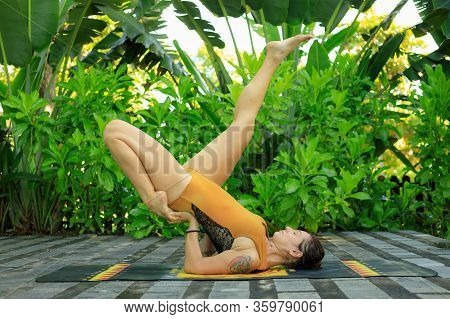 Outdoor Yoga Practice In The Garden. Young Woman Practicing Variation Of Salamba Sarvangasana, Shoul