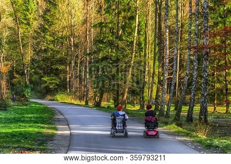Handicapped People On Wheelchairs On The Road In Nature