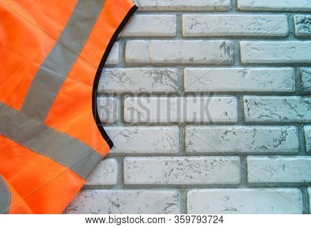 Part Of An Orange Protective Vest Against A White Brick Wall, An Emergency Safety Vest With A Copy O
