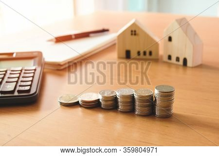 Selectove Focus Of Stack Of Money Coin For Saving For Home, Property With Small Wood House And Calcu