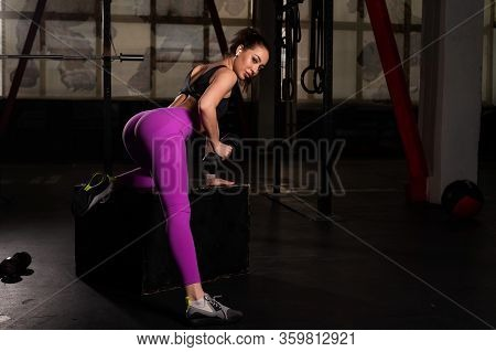 Young Beautiful Woman Doing One-arm Dumbbell Back Exercise On Bench. Athletic Girl In The Gym. Exerc