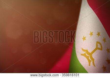 Tajikistan Hanging Flag For Honour Of Veterans Day Or Memorial Day On Red Dark Velvet Background. Ta