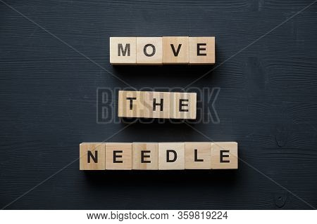 Modern Business Buzzword - Move The Needle. Top View On Wooden Table With Blocks. Top View. Close Up