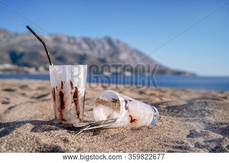 Two Dirty Abandoned Glasses With A Chocolate Cocktail Lie On A Beach Against The Blue Sky And Sea.