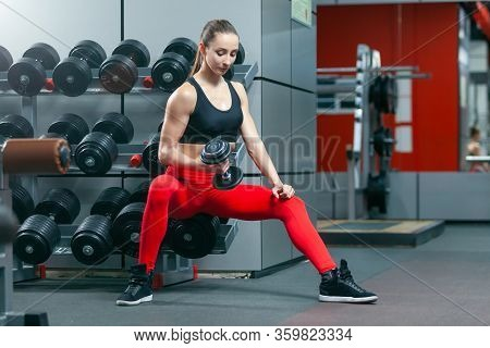 Young Muscular Fit Woman Doing Concentrated Lifting For Biceps One Hand With Dumbbell While Sitting