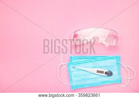 Glasses And Medical Disposable Mask For Protection Against Viruses On A Pink Background. Covid-19
