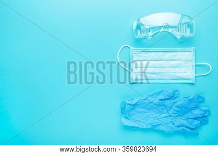 Glasses And Medical Disposable Mask For Protection Against Viruses On A Blue Background. Covid-19