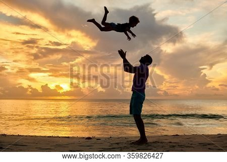 Happy joyful child, father throws up son in the air. Three year old toddler boy on beach with father at sunset. Summer family vacation at at Seychelles, Mahe.
