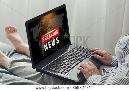 Coronavirus, Covid-19 Breaking News. A Woman With A Laptop Is Watching The News Sitting On A Sofa In