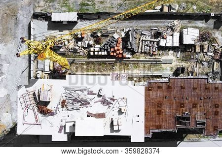 Building Object Surrounded By Metal Fence, Top View From Height. Yellow Crane, Building Materials An