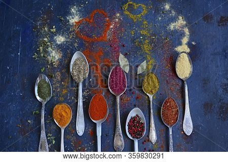 Top View On Bright Fragrant Spices On Metal Spoons On A Dark Background. Spices In The Shape Of A He