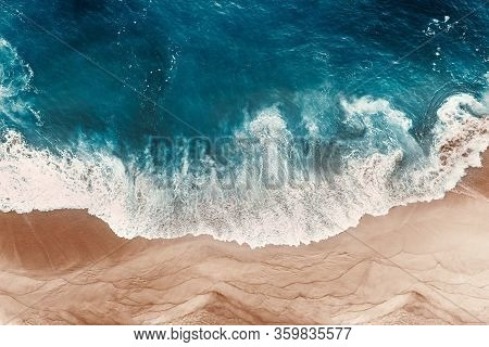 Aerial View Of The Blue Ocean Waves On The Beach. Beautiful Sandy Beach With Blue Sea. Lonely Sandy