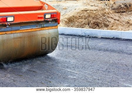 The Metal Cylinder Of The Large Vibration Roller Powerfully Tamps The Fresh Asphalt Of The Road Surf