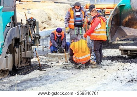 At A New Work Site, Among Large Pavers, A Workers Team In Protective Masks Discusses And Sets The Ne