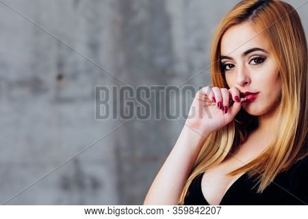 Blonde Woman With Her Hand In Her Mouth. Copy Space For Text