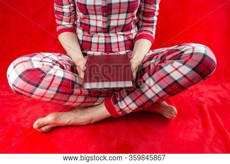 A Woman In Red Checked Home Suite With A Book At Home On A Red Background In Quarantine Coronavirus