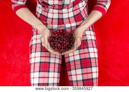 A Woman In Red Checked Home Suite Eats Berries At Home On A Red Background In Quarantine Coronavirus