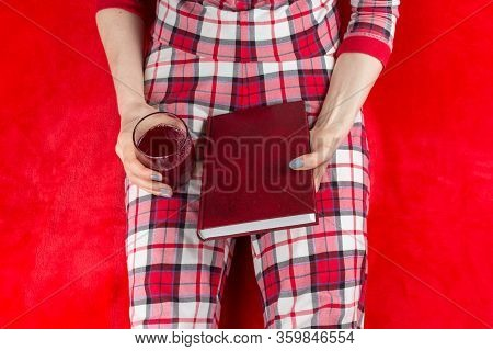 A Woman In Red Checked Home Suite With A Book And Glass Of Wine At Home On A Red Background In Quara
