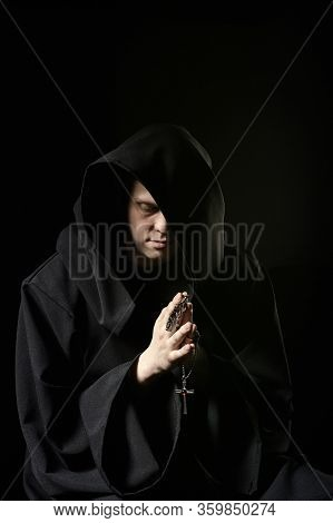 Assassin In Dark Clothes In Church. Sorcerer In Black Mantle Doing Mysterious Rite In Dark Room. Mon