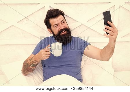 Streaming Coffee. Happy Hipster Drink Coffee Making Videocall In Bed. Bearded Man Enjoy Coffee And T