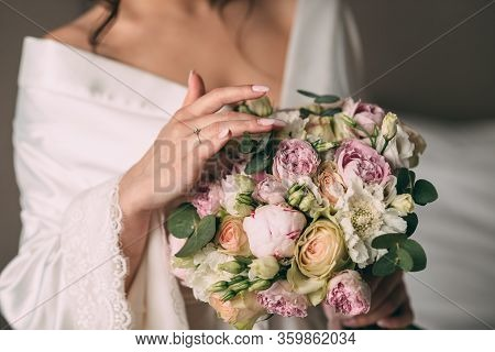 The Bride Holds In Her Hands A Bridal Bouquet Of The Bride In Pink Style, The Bouquet Is Tied With A