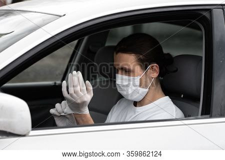 Man In Protective Medical Mask Is Wearing Rubber Gloves For Protect Himself From Bacteria Virus Whil