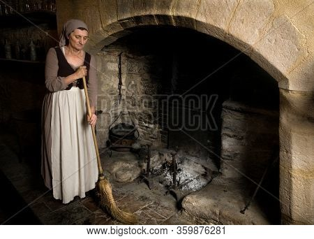 Woman dressed in renaissance maid costume using her broom to clean the fireplace in the kitchen of a property released authentic medieval castle in France