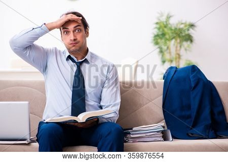 Young male employee working from house
