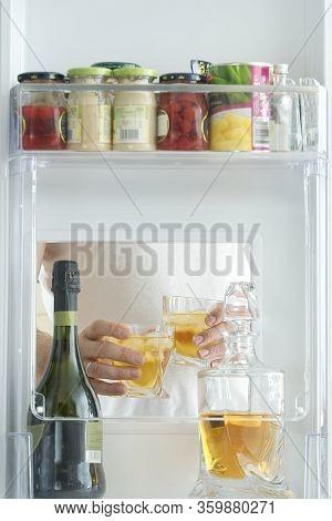 Open Hatch Of A Mini Bar In A Modern Refrigerator. Home Mini Bar In The Fridge. A Man Took Two Glass