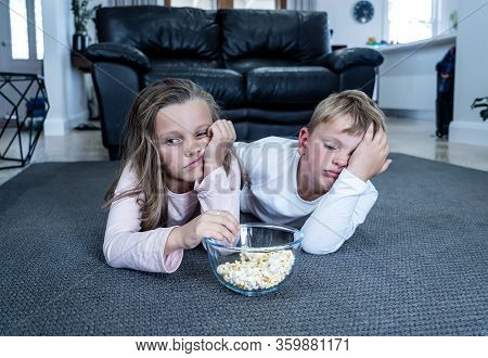 Coronavirus Lockdow. Bored Little Girl And Sad Boy Watching Tv In Isolation At Home During Quarantin