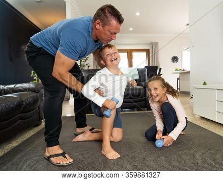 Family Exercising Together During Covid-19 Lockdown. Father And Children In Isolation Having Good Ti