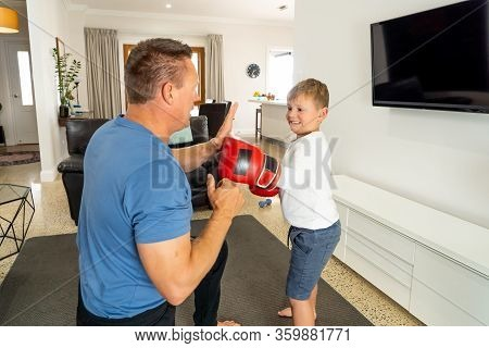 Covid-19 Shutdown. Father And Son Having Fun Boxing Together And Staying Physically Active At Home D