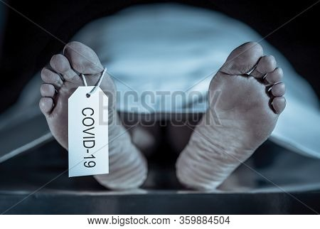 Global Health Crisis. Image Of Feet With Covid-19 Written On Toe Tag Of A Dead Body Victim Of Corona
