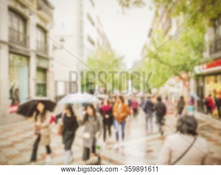 Abstract Blurred Background Of Walking People Holding Umbrella Along The Rainfall Shopping Street Am
