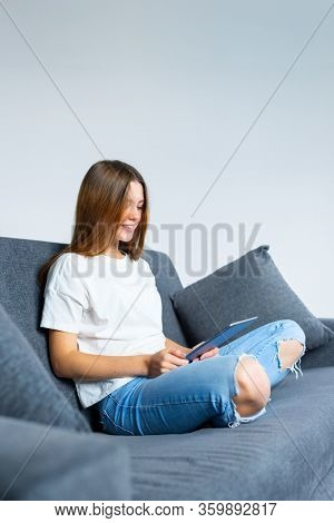 Smiling teenage girl is using digital tablet computer for distance learning. While staying at home on self isolation