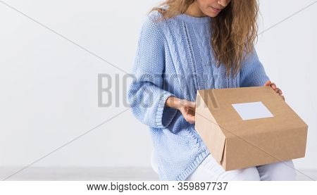 Online Shopping, Delivery And Fashion Concept - Woman Sitting At Home Opening Online Clothing Purcha