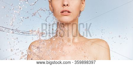 Stream of clear water splashes against a woman's body. Woman with drops of water around her face and body. Spa treatment. Girl washing her body with water.  Water and body.