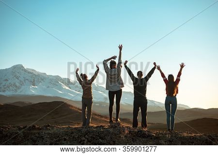 Four Happy Friends Are Standing With Raised Arms And Looking At Sunset Mountains And Sky. Unrecogniz
