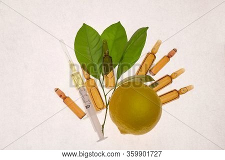 Vitamin C. Serum With Vitamin C In Ampoules And Syringe, Fresh Lemon With Green Leaves On A White Ba