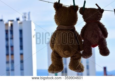 Cute Brown Toy Teddy Bears Toy Hanging On A Clothesline Whit High Building View