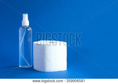 Bottle Of Anitizer And White Toilet Paper On The Blue Background
