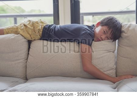 Mixed Race Asian Preteen Boy Feeling Bored Lying On Sofa At Home, Social Distancing, Quarantine, Iso