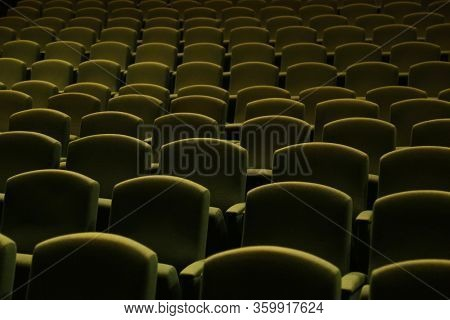 Side view of a green velvet seat in a theatre or a cinema