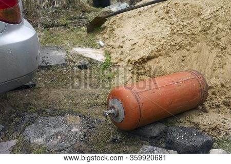 Lpg Bottle Carelessly Droped On The Ground Behind A Car