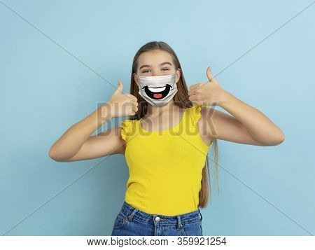 Thumb Up. Portrait Of Young Caucasian Girl With Emotion On Her Protective Face Mask Isolated On Stud