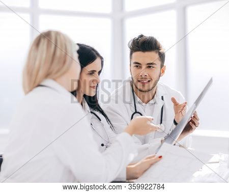 Medical Professionals Are Discussing Something Sitting At The O