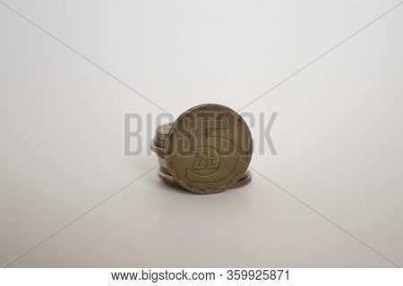 A Polish Coin Worth Five Zloty. A Coin On A White Background Stands Vertically Next To Other Coins P