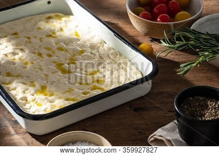 Cooking Focaccia Bread Or Pizza. Raw Focaccia With Ingredients On The Table, Tomatoes, Olives, Rosem