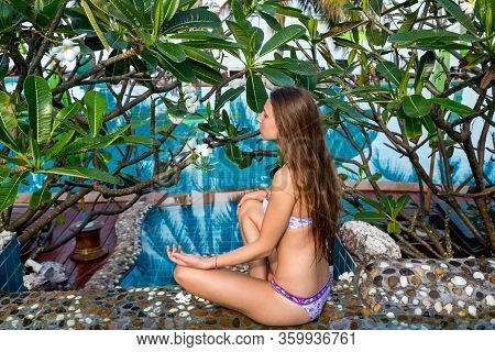 Beautiful Young Woman In Lotus Position Meditates, Sitting By The Pool In The Fresh Air Among Tropic